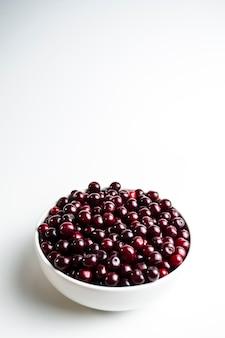 Ciliegia rosso scuro in una tazza bianca su sfondo bianco