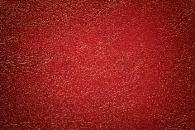 Fondo di cuoio rosso scuro di struttura, primo piano. mattone incrinato sullo sfondo dalla pelle delle rughe.