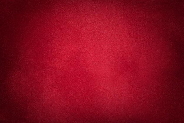 Sfondo opaco rosso scuro del tessuto scamosciato, primo piano.