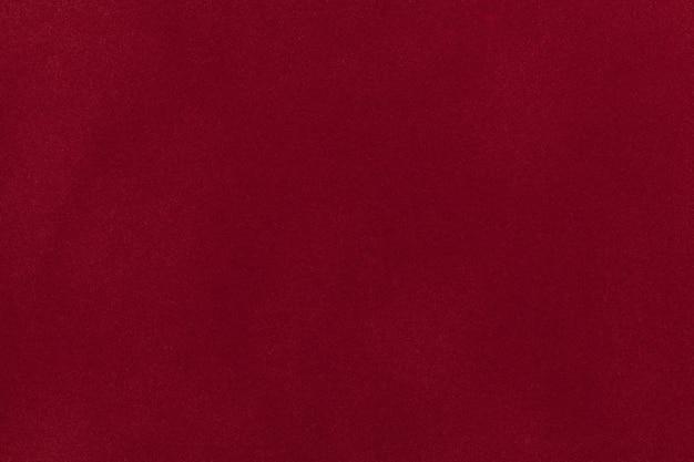 Primo piano del tessuto scamosciato rosso scuro. sfondo texture velluto