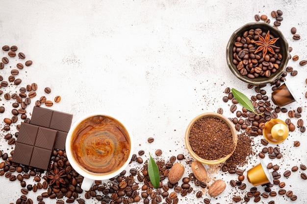 Chicchi di caffè tostati scuri, macinati e capsule con palette montate su cemento bianco