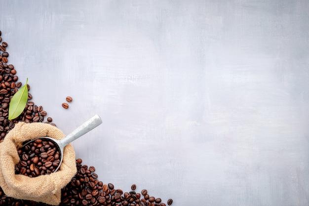 Chicchi di caffè tostati scuri in sacchi di canapa con palette montate su cemento bianco.