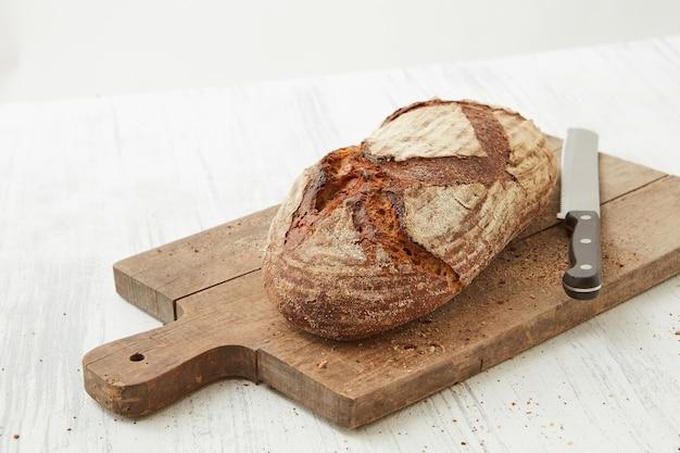 Pane di segale scuro su un tagliere con un coltello isolato su uno sfondo bianco