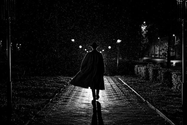 Sagoma scura di un detective maschio in cappotto e cappello sotto la pioggia in una strada notturna in stile noir