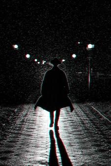 Sagoma scura di un uomo in un cappotto e un cappello sotto la pioggia in una strada di notte. bianco e nero con effetto di realtà virtuale glitch 3d
