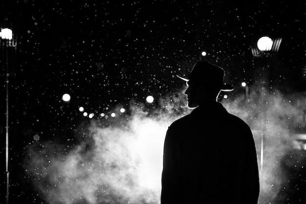 Sagoma scura di un uomo con un cappello sotto la pioggia in una strada notturna in una città in stile noir