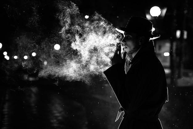 Sagoma scura di un uomo con un cappello che fuma una sigaretta sotto la pioggia in una strada notturna in stile noir