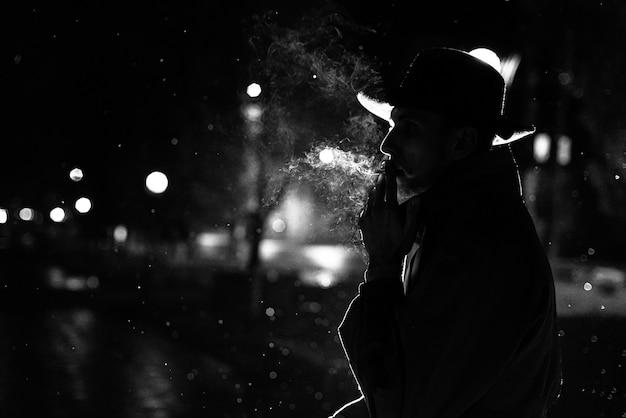 Sagoma scura di un uomo con un cappello fumare una sigaretta sotto la pioggia in una strada notturna in stile noir