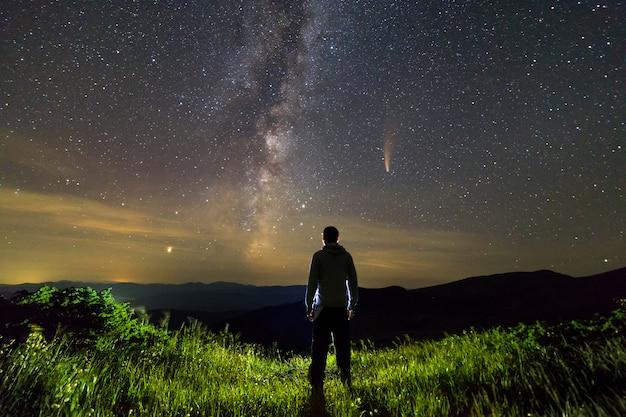 Sagoma scura di un uomo in piedi in montagna di notte godendo la via lattea e la cometa neowise con coda leggera nella vista del cielo scuro.