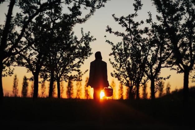Sagoma scura di donna con un cesto di fiori al tramonto nel parco