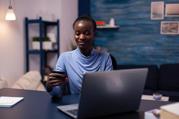Pelle scura giovane donna in possesso di carta di credito in plastica acquisto prodotto dal negozio online. dipendente che effettua una transazione di pagamento da casa sul taccuino digitale.