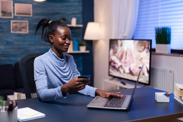 Donna d'affari dalla pelle scura con carta di credito che fa acquisti finanziari per affari dall'ufficio domestico. dipendente che effettua una transazione di pagamento da casa sul taccuino digitale.