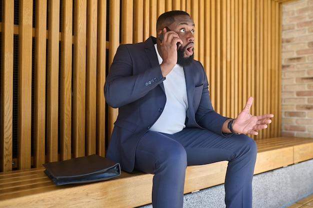 Un uomo d'affari dalla pelle scura che parla al telefono e sembra coinvolto