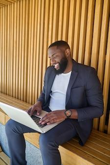 Un uomo d'affari dalla pelle scura con un laptop seduto in panchina e al lavoro