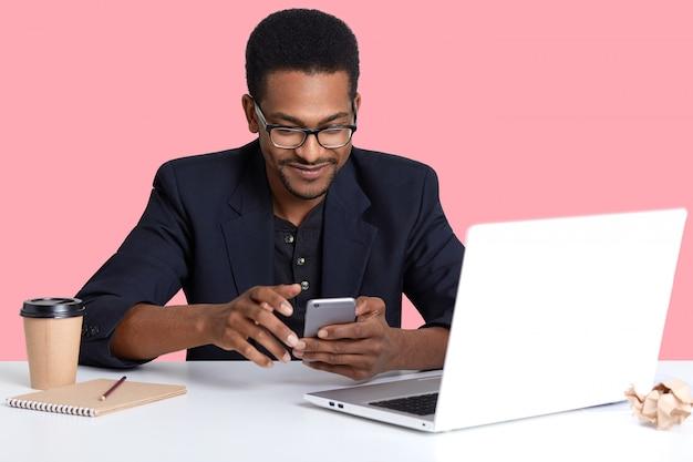 Donna dalla pelle scura con moderno telefono cellulare in mano. l'uomo di colore bello usa il rivestimento del computer portatile, per lavoro, decide i controlli del lavoro sociale della rete mentre ha il freno, isolato sul rosa