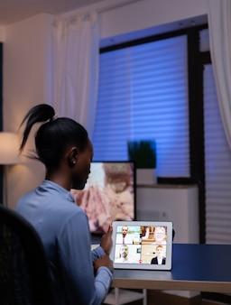 Libero professionista dalla pelle scura che ha una conferenza werbcam su tablet pc dall'ufficio di casa a tarda notte. signora che utilizza notebook con rete wireless parlando in riunione virtuale.