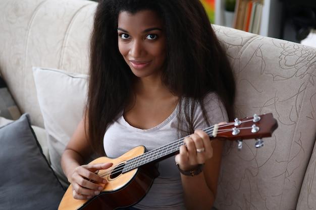 Ragazza dalla carnagione scura che si siede sul sofà che gioca ukulele
