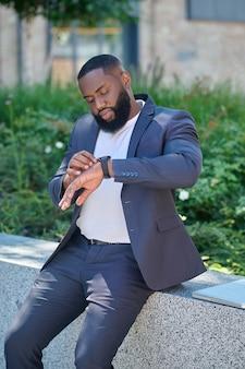 Un uomo dalla pelle scura in completo che guarda l'orologio