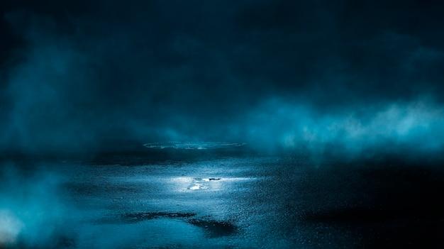 Riflessioni di asfalto bagnato strada scura di raggi nell'acqua smog fumo blu scuro astratto faretti di luce al neon vuota scena scura
