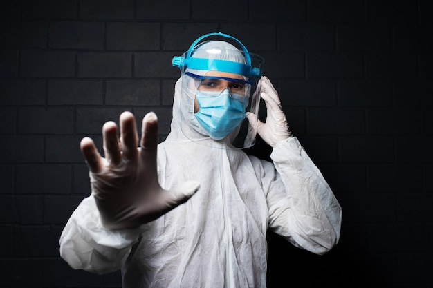 Ritratto scuro in studio di giovane medico che indossa una tuta dpi contro il coronavirus e il covid-19. mostrando il segnale di stop con la mano. sullo sfondo di un muro di mattoni neri.
