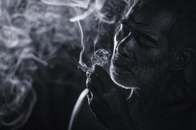 Inquadratura cupa e cupa di un vecchio che fuma