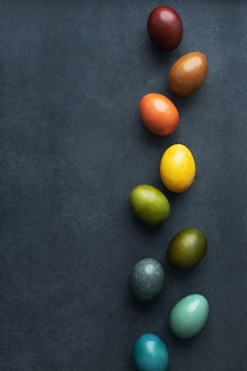 Sfondo scuro di pasqua verticale con uova colorate con colorante naturale - buccia di cipolla, caffè, curcuma, cavolo rosso, carcassa