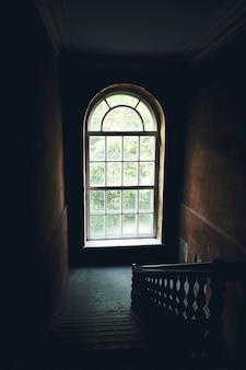 Interno d'annata scuro della scala in vecchia costruzione, scala con l'inferriata di legno, grande finestra con la luce del giorno