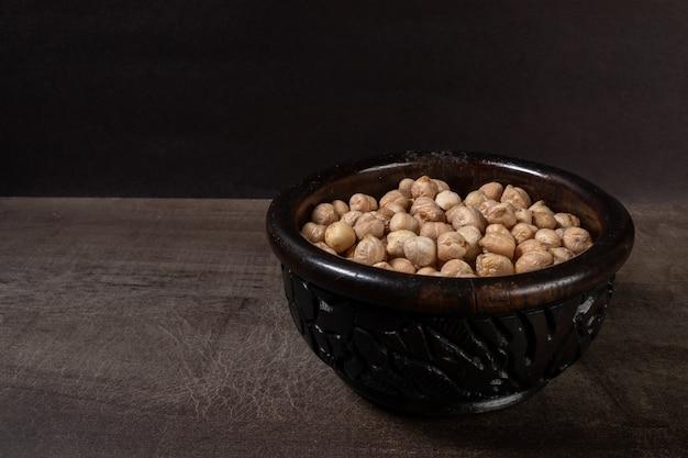 Casseruola di legno scuro con ceci crudi su una tavola di legno