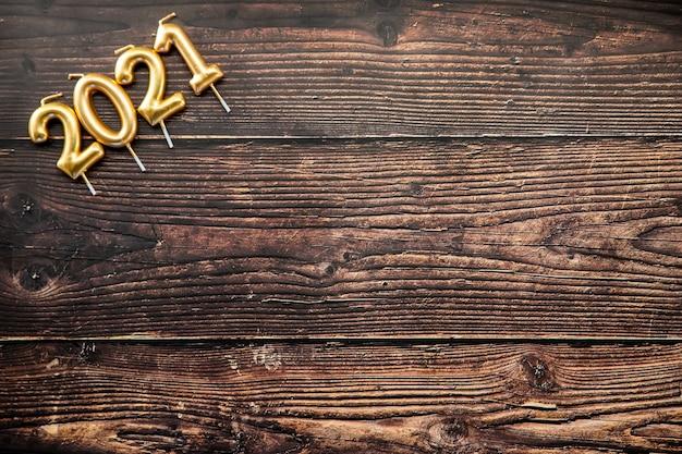 Pannello in legno scuro con dettaglio di quattro candele con il nuovo anno 2021