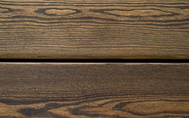 Assi di legno scuro con un bel motivo. trama di sfondo di legno marrone vintage con nodi e fori dei chiodi. tavole orizzontali scure in legno vintage. vista frontale con copia spazio. sfondo per il design