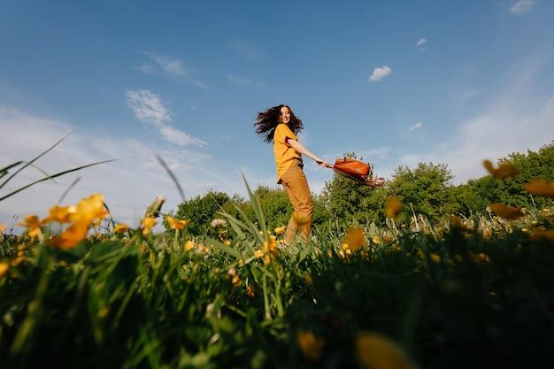 Giovane donna dai capelli scuri corre gioiosamente in un campo verde con fiori gialli contro un cielo blu