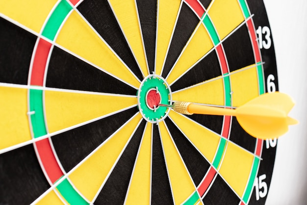 Un bersaglio per le freccette con una freccia nella fine del bullseye in su, obiettivi e concetto di targeting