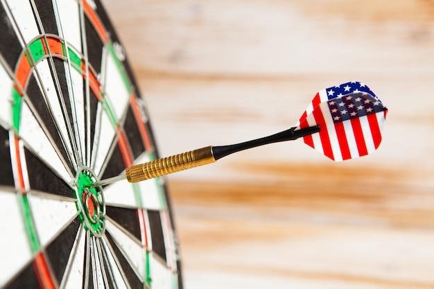 Freccette al centro del bersaglio su uno sfondo di legno