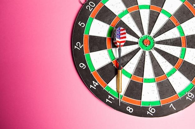 Freccette e freccette sul rosa. concetto di obiettivo