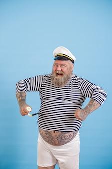 Dashing plus size persona che indossa un costume da marinaio con pose di tubo su sfondo azzurro