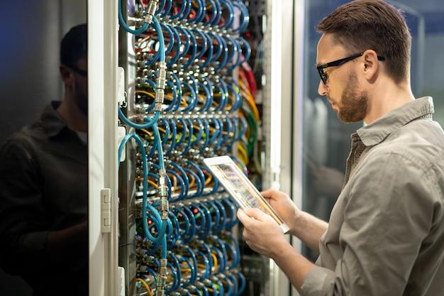 Tecnico del data center che controlla le connessioni sul tablet