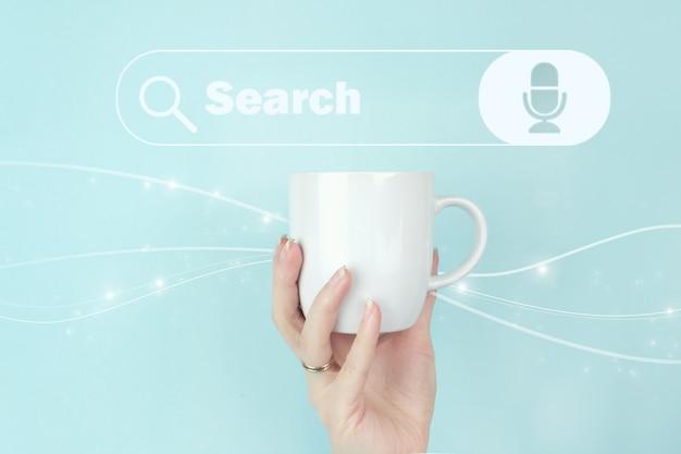 Tecnologia di ricerca dei dati ottimizzazione per i motori di ricerca. vista ritagliata della mano femminile con tazza di caffè bianco e segno cerca indirizzo e icona della barra di navigazione su sfondo blu.