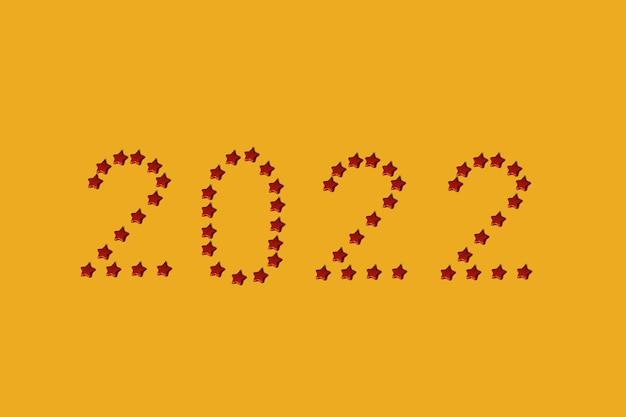 Data 2022 realizzata con palline di natale rosse a forma di stella su sfondo giallo con spazio per le copie. concetto di laici piatto di capodanno minimo.