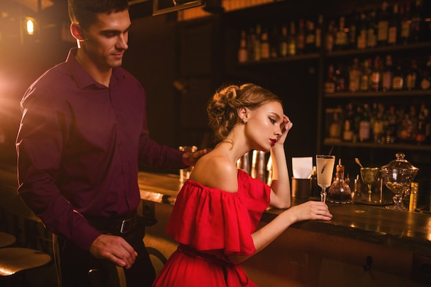 Data in discoteca, coppia attraente contro il bancone del bar. donna in abito rosso e il suo uomo, relazione d'amore, stile di vita notturno