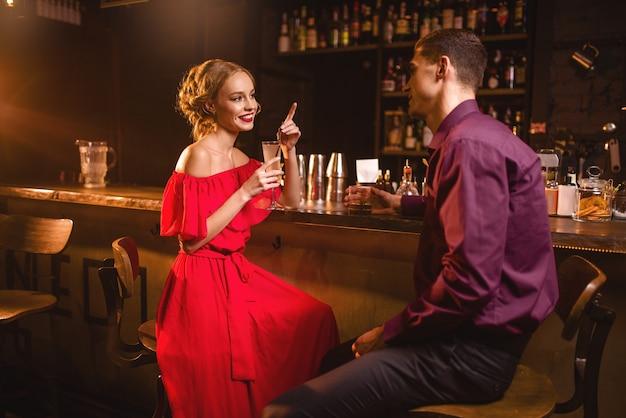 Data in discoteca, donna attraente in abito rosso flirta con l'uomo contro il bancone del bar in discoteca. relazione d'amore, stile di vita notturno