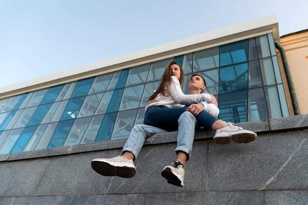Data di una giovane coppia. la ragazza è seduta sulle ginocchia del ragazzo. costruzione moderna della città sullo sfondo. vista dal basso.