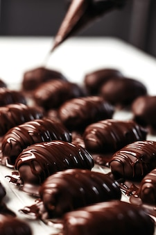 Datteri al cioccolato, dessert. il pasticcere versa il cioccolato sul dessert. foto verticale.