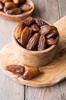 La frutta della palma da datteri in ciotola di legno è spuntino sano.