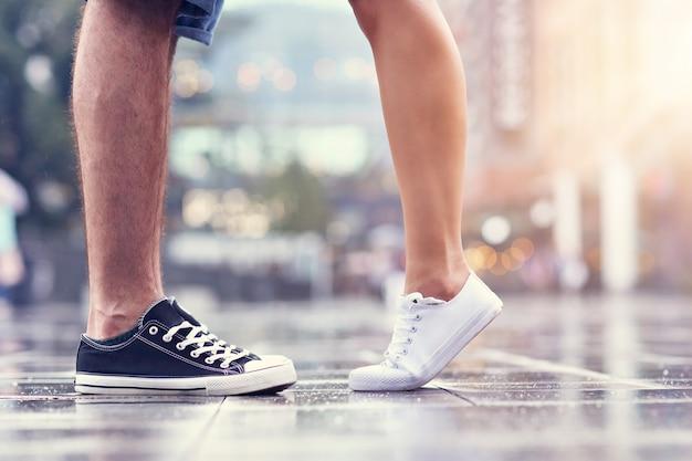 Uscire con le gambe di una coppia per strada sotto la pioggia