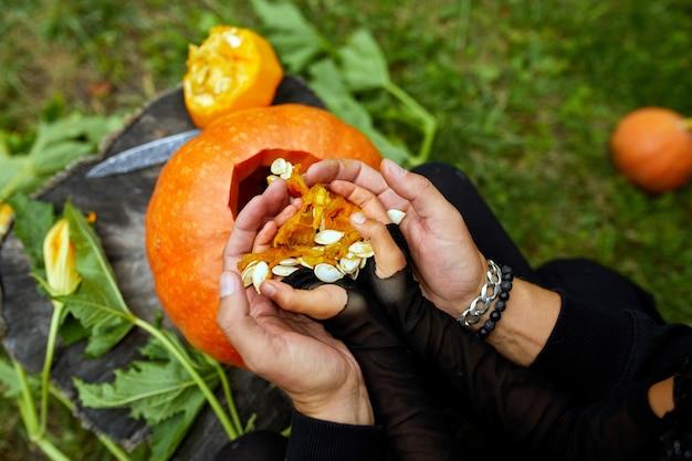 Figlia e padre intagliano la zucca per halloween, prepara jack o'lantern