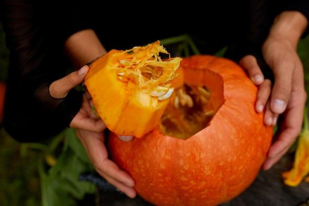Figlia e padre aprono le mani, tagliano la zucca prima di intagliarla per halloween, prepara jack o'lantern. decorazione per la festa, piccolo aiutante di famiglia,