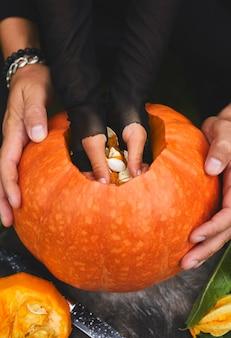 Le mani del padre e della figlia estraggono semi e materiale fibroso da una zucca prima di scolpire per halloween. vista dall'alto, primo piano, vista dall'alto, copia dello spazio