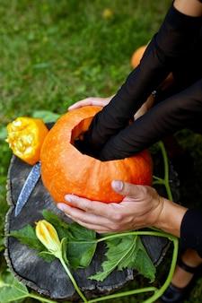 Figlia e padre mani tira semi e zucca materiale fibroso prima di intagliare per halloween, prepara jack o'lantern. decorazione per la festa, piccolo aiutante familiare, vista dall'alto, da vicino, copia spazio