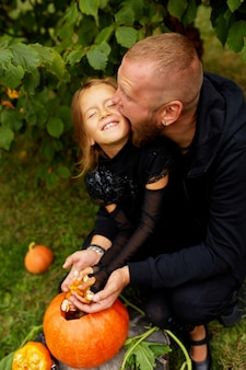 Mani di figlia e padre che estrae semi e materiale fibroso da una zucca