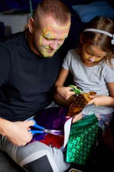 Figlia e padre si divertono a fare artigianato insieme a casa sul divano, tagliando un foglio con le forbici, luce oscura, festa del papà, famiglia.